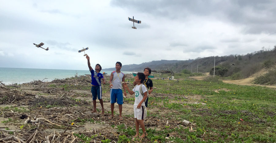 Children flying their planes at the beach